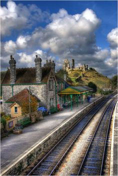 The sunlit ruins of Corfe Castle in Dorset tower above the railway station at Corfe Castle on the preserved Swanage Railway.