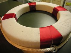 """Nautical life ring buoy / Cake Pop Stage.  Uses a foam wreath base wrapped in white crepe paper.  Red ribbon on four """"sides"""".  Eyelet screws and rope around the perimeter.  I put 16 total holes in the top, alternating depths so the final presentation will have more variety."""