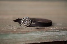 "A strap of distressed chocolate brown leather beholds a floral sterling silver .75"" button."