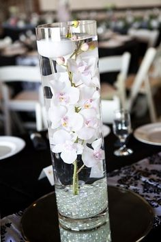 Lovely wedding centrepiece: floating orchids and candles in a thin vase. Perfect place for Candle Impressions new floating flameless candles