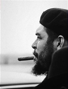 Profile portrait of Argentine-born Cuban Marxist revolutionary Ernesto 'Che' Guevara (1928 - 1967) wearing a beret and smoking a cigar in an airport, probably New York City.