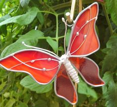 My grandsons were able to watch a Monarch coming to life- so I made them this suncatcher with the brilliant colors the Monarch revealed.    This is great for gifts or to brighten your windows this fall. The top is opal semi-opaque with red and orange streaks through the glass and the bottom is an orange translucent glass. The body is a lead-free casting. It measures approx. 4.5 x 5. The wire adds creative accents and also strengthen the suncatcher so years later it hangs as it did the first…