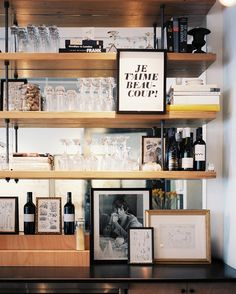 I love so much about this space: shelves suspended from ceiling by pipes, open shelving bar area against a mirror, frame hung from the front of the shelves. Drool.