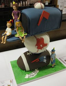 Sculpted birthday cake of a mailbox stacked on top of a New England Patriot's football and a Boston Red Sox baseball.