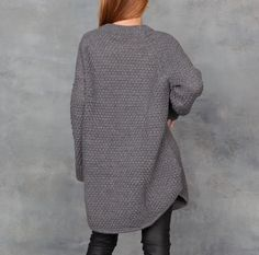 Oversized chunky knit sweater dress with rounded hem details. Dark Charcoal grayyarnwith rice-stitch and extra-longsleeve detail, alpaca, acrylic and wool blend.
