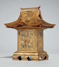 CABINET, Fuji mark of the Komai workshop, late 19th century. In the form of a temple, decorated in gilt nunomezogan, the roof chased with dragons, pheasants and ho-o birds, the two hinged doors open to reveal three small drawers engraved with village landscapes, wood stand 15.8cm high.