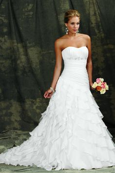 Reflections by Jordan: M980  Silhouette: Ball Gown  Neckline: Sweetheart  Price Range: $$$ = $1001-$1500  Waist: Empire  Embellishment: Beading, Ruffles  Style: Formal  Color: White  Hemline: Floor-length  Train: Chapel  Fabric: Organza  Description: Cascading flounces sweep the floor of this Luxe Organza ball gown with a chapel train. Ruched angled bodice with sweethheart neckline and beaded empire waist. Removable spaghetti straps are included. Available with a zipper or lace-up back.