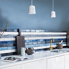 Stunning handmade tiles available from Laurence Pidgeon make a really striking kitchen backsplash in shades of blue in this modern kitchen with stand out gold tap.