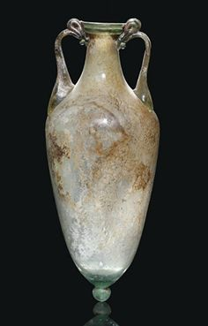 to Century - A ROMAN GREEN GLASS AMPHORA Free-blown, with elongated ovoid body, knopped base, tapering neck and folded rim, the twin green handles applied at shoulder and rim where they form a loop Glass Vessel, Glass Ceramic, Glass Art, Ancient Rome, Ancient History, Art Romain, Roman Art, Ancient Artifacts, Ancient Civilizations