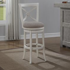 The Flores bar stool offers a casual look that will complement most any decor. Made of solid hardwood with an antique white finish and light brown linen seat, this swivel stool features with a french curve x back and carved dogwood rosette.