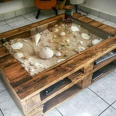 A DIY pallet wood glass display coffee table idea for the avid beachcomber! Leaves plenty of space to create a great beach scene with sand and shells. Featured on Completely Coastal. Pallet Home Decor, Pallet Patio Furniture, Diy Furniture Projects, Diy Pallet Projects, Easy Home Decor, Living Furniture, Handmade Furniture, Rustic Furniture, Wood Projects