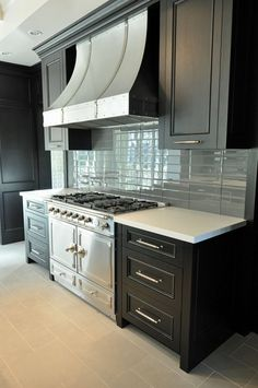 blue-grey subway tiles with stainless steel appliances (la cornue stove) and dark painted cabinets.