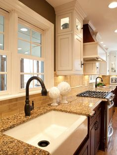Interesting idea of white cabinets up and dark under counter.  Love the farm sink!