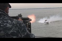 Speed boat approaches large Navy craft during training exercise.
