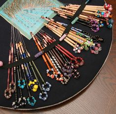 My wifes bobbin lace making by exfordy, via Flickr -- love the colorful bobbins & the use of the pinned elastic to hold and divide. Genius.