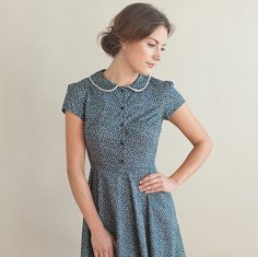 This vintage inspired dress is handmade in a navy cotton fabric with pretty floral print. The fitted waist and circle skirt give it a flattering