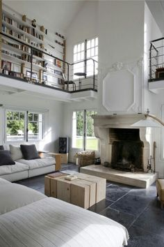 White walls, light wood, muted gray couch, high ceilings, second story library, lots of natural light, architectural detail over fireplace