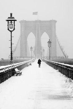 Man walking on Brooklyn Bridge in winter by Anthony Pitch