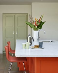 There are a lot of statement elements in this bright kitchen, from the beautifully fitted out larder cupboard and the colourful splashback to the orange island. The joyous mixture of colour and light  in this kitchen signposts its purpose, providing a warm and inspiring area at the heart of the house for family and friends gather to socialise, cook and eat together. Larder Cupboard, Bright Kitchens, Handmade Kitchens, Bespoke Kitchens, Splashback, Dressing Room, Showroom, Purpose, Cook