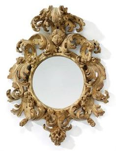 AN ITALIAN YELLOW-PAINTED MIRROR -  CIRCA 1700 -  The later circular plate within a pierced foliate-carved surround surmounted by a female mask and scrolled pediment, originally gilt, decoration largely rubbed 22 in. (56 cm.) high, 16 in. (40.5 cm.) wide