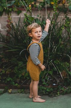 Little boy playing out in the backyard in perfect little playsuit. Black and white striped long sleeve top with short leg salopette boho outfit from Noble Carriage. Salopette so cute and so chic in beautiful mustard color, made from organic cotton by Gray Label so baby's daily uniform is free of chemicals and safe for delicate skin. PHOTOGRAPHY BY: http://studiocastillero.com/