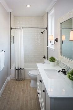large transitional 3/4 bathroom in Los Angeles with an undermount sink, furniture-like cabinets, white cabinets, granite countertops, a drop-in tub, an alcove shower, an one-piece toilet, gray tile, stone tile, gray walls and painted wood floors