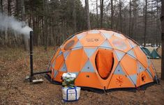 Mountain Hardwear Space Station Tent set up in the woods, with an improvised chimney.