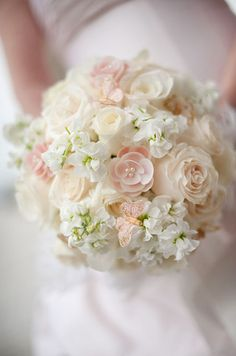 A bouquet of white freesia and blush roses is accented with pearl pins and a…