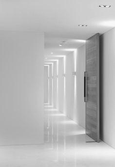 Stark white office hallways with heavy grey doors. Arch Interior, White Interior Design, Interior Lighting, Lighting Design, Interior Architecture, Interior And Exterior, Corridor Lighting, Indirect Lighting, Blitz Design