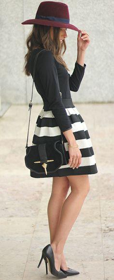 Cute black heels, black white striped patterned skirt, black shirt, black purse, red hat