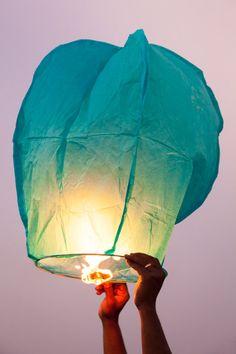A man releases a magic lantern into the sky at the end of the Uttarayan Festival. - Uttarayan Kite Festival - Tom Robinson Photography