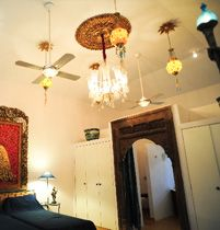 India's national bird acquires more plumes at the first room of Ishavilas. A chandelier clinks and twinkles over a decorative peacock portrait with twin beds below. The interior can be described as very Maharaja and decor of the 1920's.