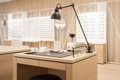 The opposing wall is masked with a semi-translucent floor to ceiling drape, which softens the chaos of the window front. In front of the curtain, a free standing display sets the specs optimally whilst providing a border for the room. Shop Interior Design, Retail Design, Store Design, Optometry Office, Eyeglass Stores, Eyewear Shop, Glasses Shop, Optical Shop, Retail Concepts