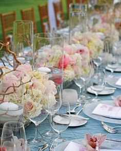 "See the ""Tropical Centerpieces"" in our Real Weddings on the Beach gallery Guests dined at a long rectangular table set with candles, driftwood, orchids, hydrangeas, and roses."