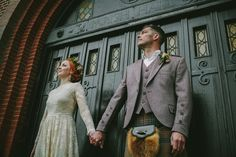 bride and groom stand against a black doorway looking at the sky