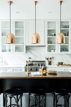 Modern kitchen with rosy metalic pendant lights and marble backsplash
