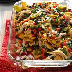 Baked Chicken Nachos Recipe Appetizers, Main Dishes with red bell pepper, green pepper, canola oil, black beans, minced garlic, dried oregano, ground cumin, rotisserie chicken, lime juice, salt, pepper, tortilla chips, pepper jack, sliced green onions, fresh cilantro, sour cream, pickled jalapeno peppers