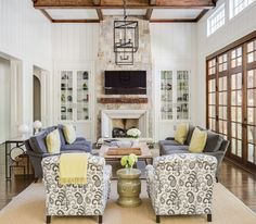 """Wood architectural accents—in the form of ceiling beams, fireplace mantel and doors--cozy up the tall ceilings in the living room. Adams designed glass-front cabinets on either side of the fireplace rather than open shelves in the living room. """"I think open shelves can be cluttered and challenging to decorate,"""" he says. """"Adding the doors seems to organize things and add a bit of texture to the room."""""""