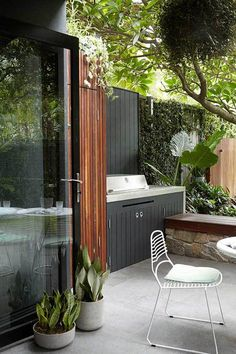 The black outdoor cabinets mixed with natural wood features, stone, concrete, and plants is actually quite pretty and modern