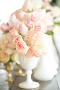 Love this... I like the milk glass vases and the simplicity and elegance of the soft pink florals with just hints of spring green.