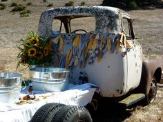 old truck decorated with fabric strip banner & sunflowers hold beer and waters at wedding site