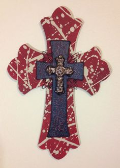 """Large wooden, triple layer, wall cross. The back cross is painted with maroon acrylic paint, and then splattered with taupe acrylic paint for a fun texture. The piece is then topped with a black textured iron cross with maroon accents to enhance the texture. The piece is then topped with a glossy black and brown ornate ceramic cross. Dimensions are approximately 15"""" x 22"""". Each cross is handmade with love and truly one of a kind."""