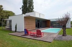 Toutes les pièces de cette grande maison s'ouvrent sur le jardin ou sur une terrasse. L'orientation, les matériaux et les équipements offrent un habitat confortable et chaleureux dans un style minimaliste.