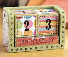 Turn Basic Blocks into a Home Decor Calendar  Design by Wendy Gibson  Wendy turned wood blocks into a decorative calendar with basic scrapbooking supplies. Paint, patterned paper, and rub-ons embellish the blocks, and faux stitching done with a black marker completes the look.
