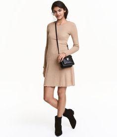Dunkelbeige. Kurzes, figurbetontes Langarmkleid aus weicher, gerippter Viskosemischung. Das Kleid hat Overlockkanten an Ärmelabschlüssen und Saum.
