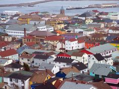 St. Pierre and Miquelon -- while the row houses of St. John's looked like a handful of jelly beans, the colour of the French city was bolder, more red than rose, crisp detached buildings with sharply defined roofs instead of vertical splashes of soft-hued rainbow clapboard.
