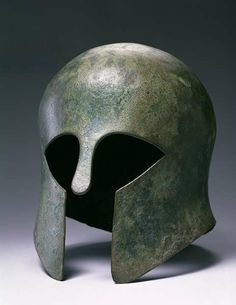 Corinthian Helmet (bronze). Greek (7th-5th century BC)  a hole in the back of this example suggests it was placed in a sanctuary as a votive offering; Private Collection