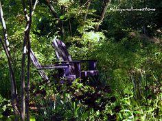 Purple adirondack chairs in the shade garden.