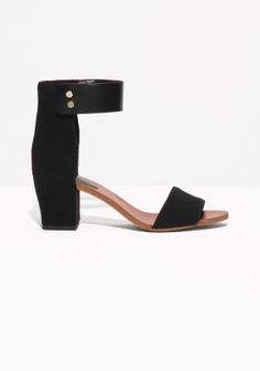 Elegant black sandals featuring an ankle strap with two gilded snap buttons to close and matching mini-pins along the upper side of welt.
