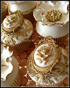 A collection of elaborate Rococo inspired gold and ivory fondant wedding cupcakes with edible sugar brooches & flowers hand painted with gold lustre finished with genuine victorian antique lace. They accompanied a two tier wedding cake in a cupcake tower.